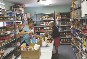 Preparing boxes of food for Food Pantry clients are volunteers Beth Shakan (left) and Marny Hayward (right.)